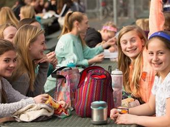 Students eating lunch on a table outside
